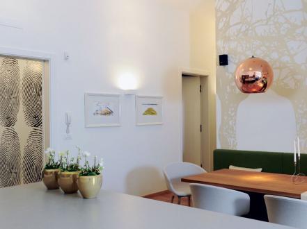 V bivalnem delu, kjer se hiša galerijsko odpira, je fototapeta z drevesom, ki se vije okrog vogala. Ta zaznamuje središče doma. Dopolnjujeta jo viseči luči nad jedilno mizo, ki sta glavni poudarek osvetlitve.