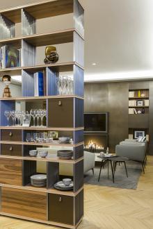 Prosto stoječi knjižni regal, na katerem prav tako opazimo kovinske elemente, ločuje jedilnico od dnevne sobe. Gre za sodobno oblikovan kos, ki deluje kot pregrada, knjižna omara, shranjevalni prostor in omara za lepe predmete ter porcelan.
