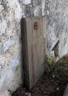 Težka lesena loputa je včasih zapirala odprtino v medetažni plošči in stopnice, po katerih so se spuščali v klet po vino. Prejšnji lastnik je stopnice odstranil, odprtino v plošči pa zazidal.