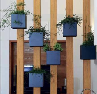 Lesena pregrada z okrasnimi lončki med dnevnim in kuhinjskim delom delno ločuje prostora, a hkrati prepušča pogled.