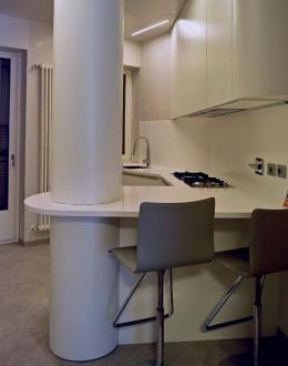 Kuhinja je zasnovana moderno. Večina stvari je skritih za gladkimi belimi površinami, ponekod so vidni le ročaji in gospodinjski aparati.