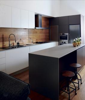 Kuhinja je kombinacija visokih in nizkih omar ter delovnega otoka. Za oblogo nad kuhinjskim pultom so izbrali hrastov les.