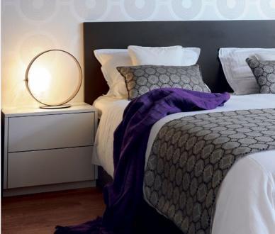 Oprema spalnice sledi prostoru in njegovim danostim. Steno za vzglavjem postelje prekriva nežna tapeta s krogi, ki jo dopolnjujeta nočni lučki prav tako v obliki kroga. Za piko na i prostora so dekorativne tkanine.