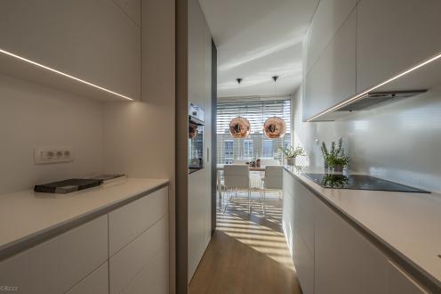 Kuhinja je zasnovana dvoredno. En niz kuhinjskih elementov z delovnim pultom se lahko v celoti skrije za krilnimi vrati.