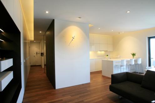 Vzdolž hodnika so na eni strani garderobne omare, ki delujejo kot bela stena.