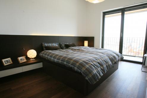Spalnica z garderobno sobo je po barvah in materialih usklajena z bivalnim delom stanovanja.