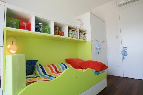 Otroški sobi sta barvno pestrejši, rjavim in belim površinam so dodali v eni sobi zeleno, v drugi modro barvo. Dodatno ju poživljajo različni predmeti in igrače.