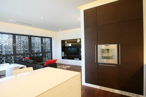 V stanovanju prevladuje bela barva, za poudarek pa so izbrali barvo orehovega lesa, ki se pojavlja na talni oblogi in nekaterih elementih ter kosih pohištva.