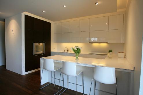 Kuhinja z otokom je v beli barvi, v sijajni izvedbi. Po prvotni zasnovi je bila predvidena tudi shramba. To so razdelili na dva dela, zato so zdaj na eni strani visoke omare v barvi oreha z vgrajenimi gospodinjskimi aparati, na drugi pa utiliti. Vrata vanj so vpeta v leseno stensko oblogo in na pogled ne dajejo občutka, da se za njimi skriva dodaten prostor.