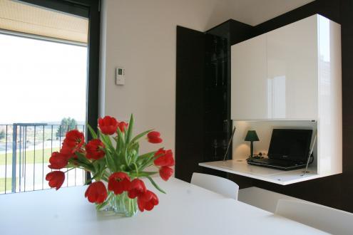 Za belo gladko površino se skriva tudi delovni kot, ki so mu prostor odmerili v bivalnem delu stanovanja.