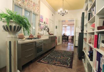 Prostoren hodnik sredi stanovanja je postal kuhinja in knjižnica hkrati. Je mesto ustvarjanja in srečevanja. Rumena stena in strop poskrbita, da je sončen, četudi se okno odpira le v svetlobni jašek hiše.