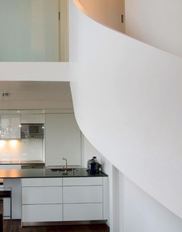 Kuhinja je umaknjena v ozadje osrednjega prostora, zastira jo tudi stopnišče, s katerim so dve stanovanji povezali v eno. Opremljena je skladno s filozofijo lastnikov, ki temelji na odprtosti, malo opreme, čistih linijah in svetlosti.