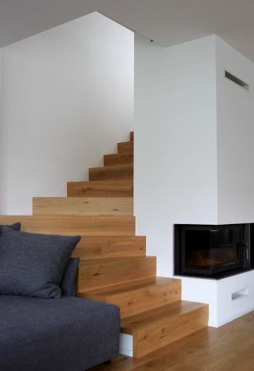 Lesene stopnice, ki vodijo iz pritličja v nadstropje, »objemajo« kamin z dimnikom, v zgornjem delu nosilca stopnic pa so integrirana drsna vrata.