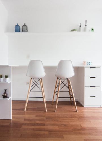 Kuhinjski pult, ki je narejen po meri, se nadaljuje z jedilno površino in omarico za dnevno sobo ter konča z delovnim kotičkom.