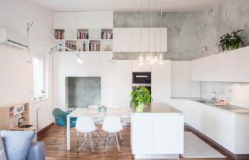 Osrednji prostor zaznamujejo nežno potiskana tapeta, visoki stropi in belo pohištvo brez ročajev.