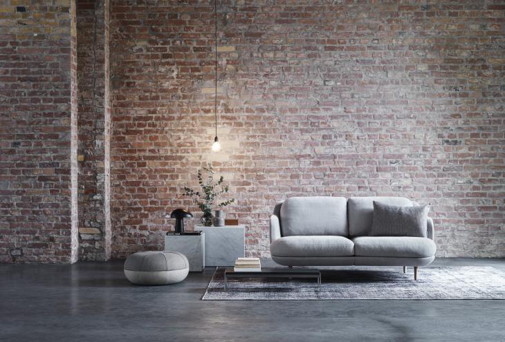 Čeprav nove smernice nakazujejo temnejše barve v interierjih, je umirjena siva še vedno pogosta izbira za oblazinjeno pohištvo (podjetje Fritz Hansen).