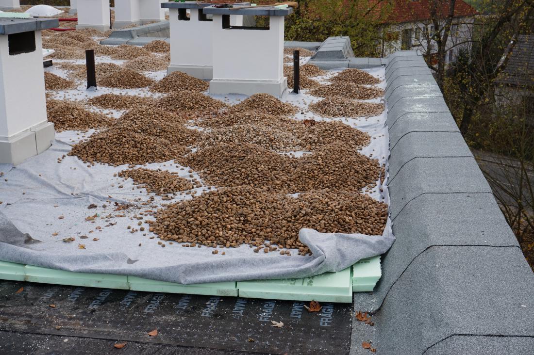 Sanacija ravne strehe na stanovanjskem bloku po principu plus ravne strehe – vidijo se nova hidroizolacija, toplotna izolacija iz ekstrudiranega polistirena, filc in prodec, spodaj sta še termoizolacija iz stiropora in stara hidroizolacija, ki deluje kot parna zapora. Foto: arhiv GI ZRMK