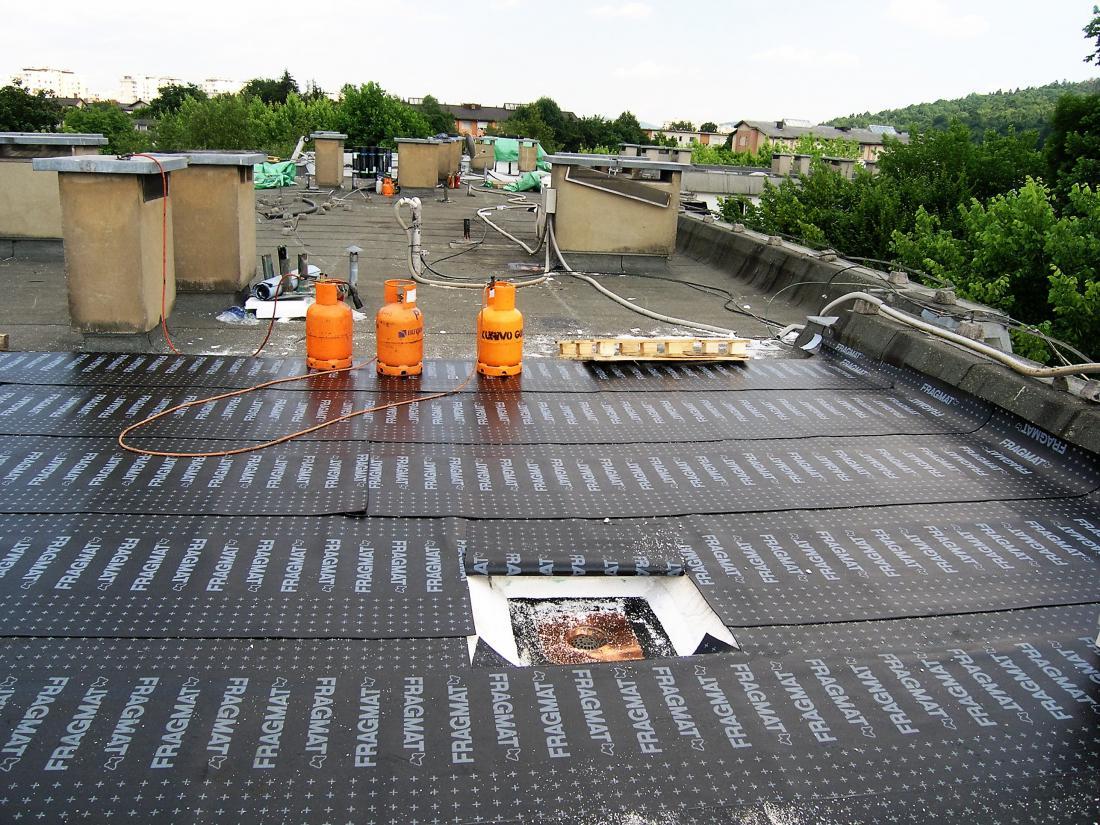 Sanacija ravne strehe na stanovanjskem bloku: vidijo se obstoječa hidroizolacija, nova toplotna izolacija in dvoslojna polimer-bitumenska hidroizolacija; sledijo še ekstrudirani polistiren, filc in prodec. Foto: arhiv GI ZRMK