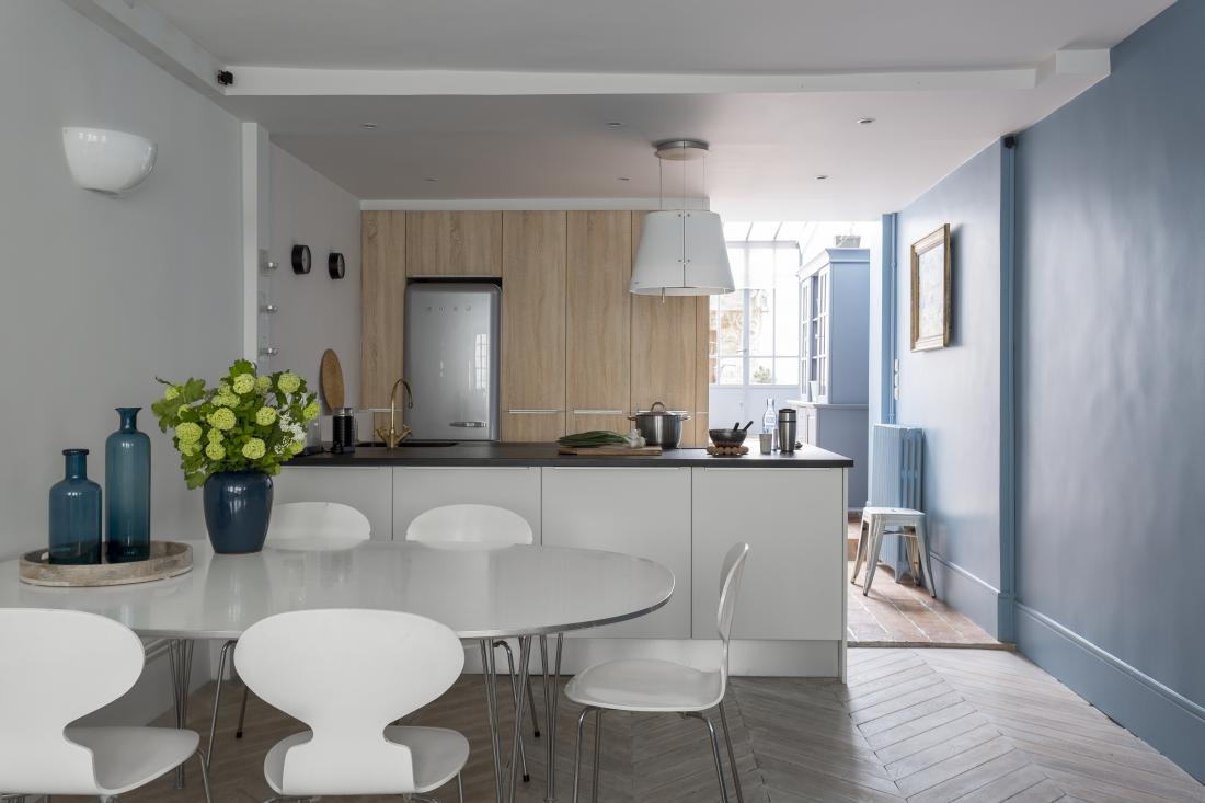 Bel kuhinjski otok je lep kontrast modrim stenam in nekoliko beljenemu lesu. Za jedilniško mizo stojijo stoli danskega oblikovalca Arneja Jacobsena Ant chair v beli barvi, oblikovani v 50. letih 20. stoletja.