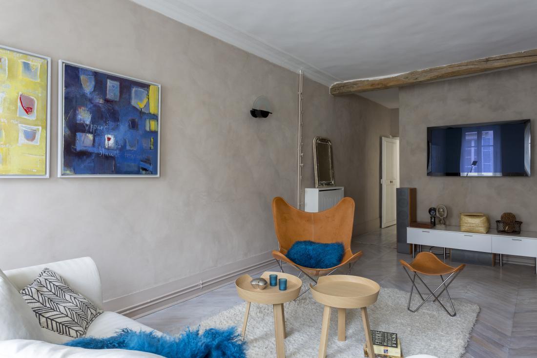 V prvem nadstropju je še ena, prostrana dnevna soba s televizorjem, namenjena tudi druženju s prijatelji. Stene so prepleskane z drobnim mineralnim apnom, zaradi katerega so dobile umetno postaran videz.