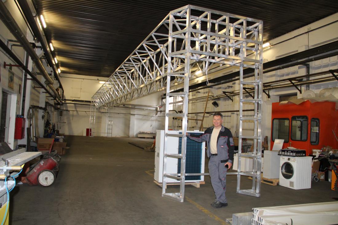 Jože Abram ob največjem 3D-tiskalniku, ki ga še izdelujejo, vendar osnovno ogrodje že stoji.