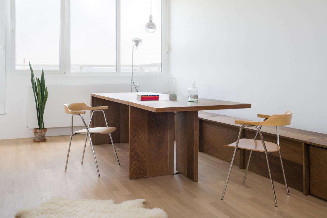 Dolgo mizo iz orehovega lesa se po potrebi lahko z dvigom stranskih kril podaljša, dopolnjuje pa jo ob celotno dolžino stene postavljena nizka klop z velikimi izvlečnimi predali za shranjevanje. FOTO: Janez Marolt