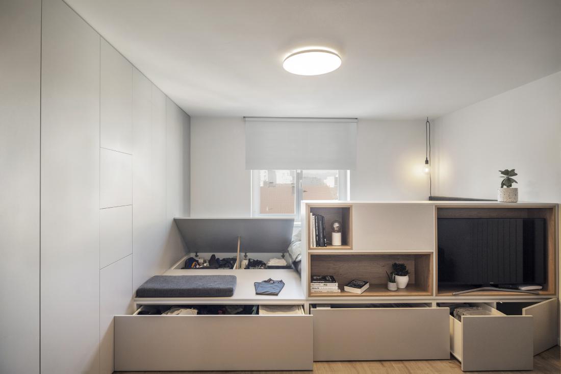 Po meri zasnovan večnamenski podest, v katerem so klop, postelja in shranjevalni prostor, celotno stanovanje razgiba in obogati. Foto: Andraž Jenkole