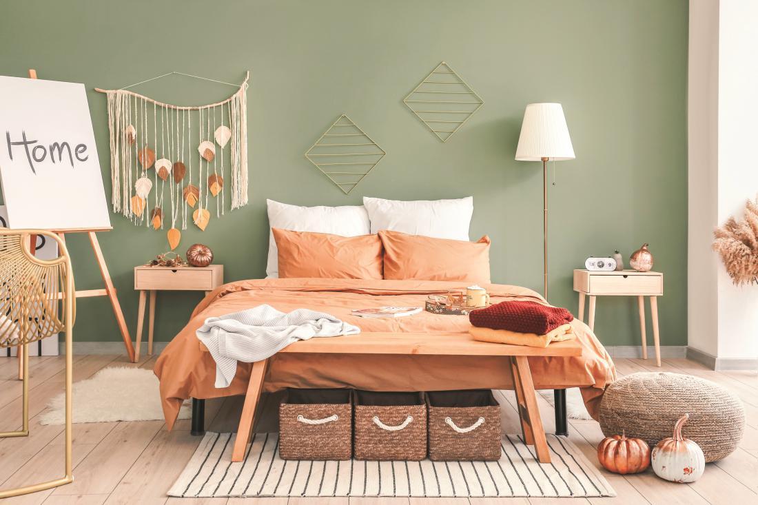 Zelena se lahko znajde tudi na steni spalnice, za poživitev ji dodajte tople rjavo oranžne odtenke. Foto: arhiv Jub