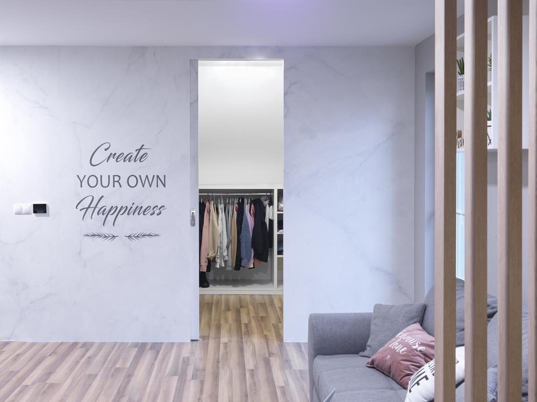 Steno, kjer je vhod v garderobo, prekriva tapeta z nežnim vzorcem marmorja in velikim napisom.