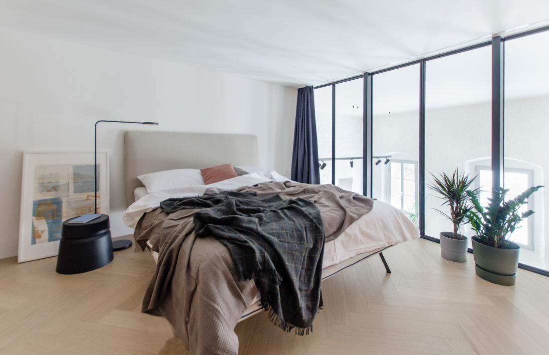 Izkoristili so višino stanovanja, ki je 4,3 metra, in spalnico umestili na podest.