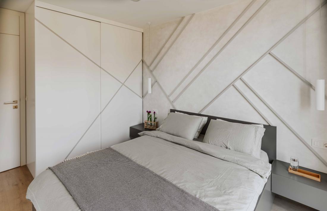 Steno za posteljo so popestrili s stensko oblogo: oplesk, na katerem so po meri narejene dekorativne letvice, ki se nadaljujejo na garderobno omaro.