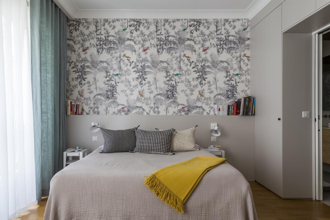 Steno za vzglavjem postelje krasi tapeta.
