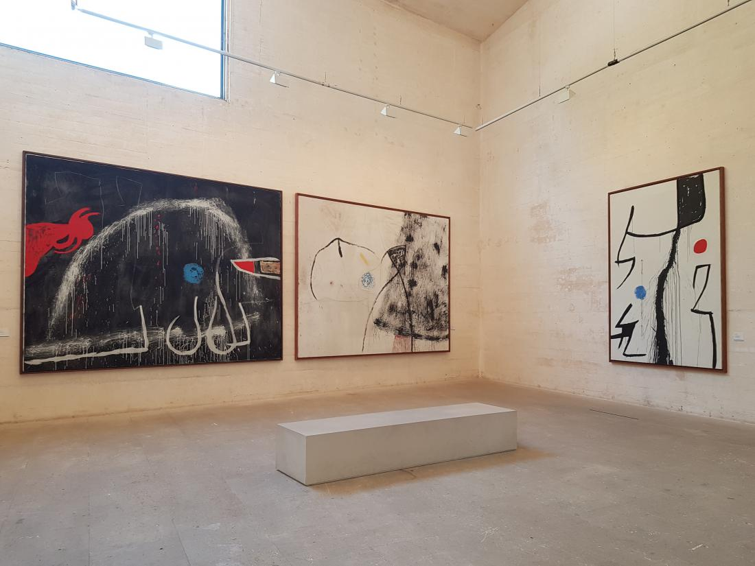Izčiščene betonske stene v notranjosti ponujajo minimalistično ozadje za Mirójeva platna.