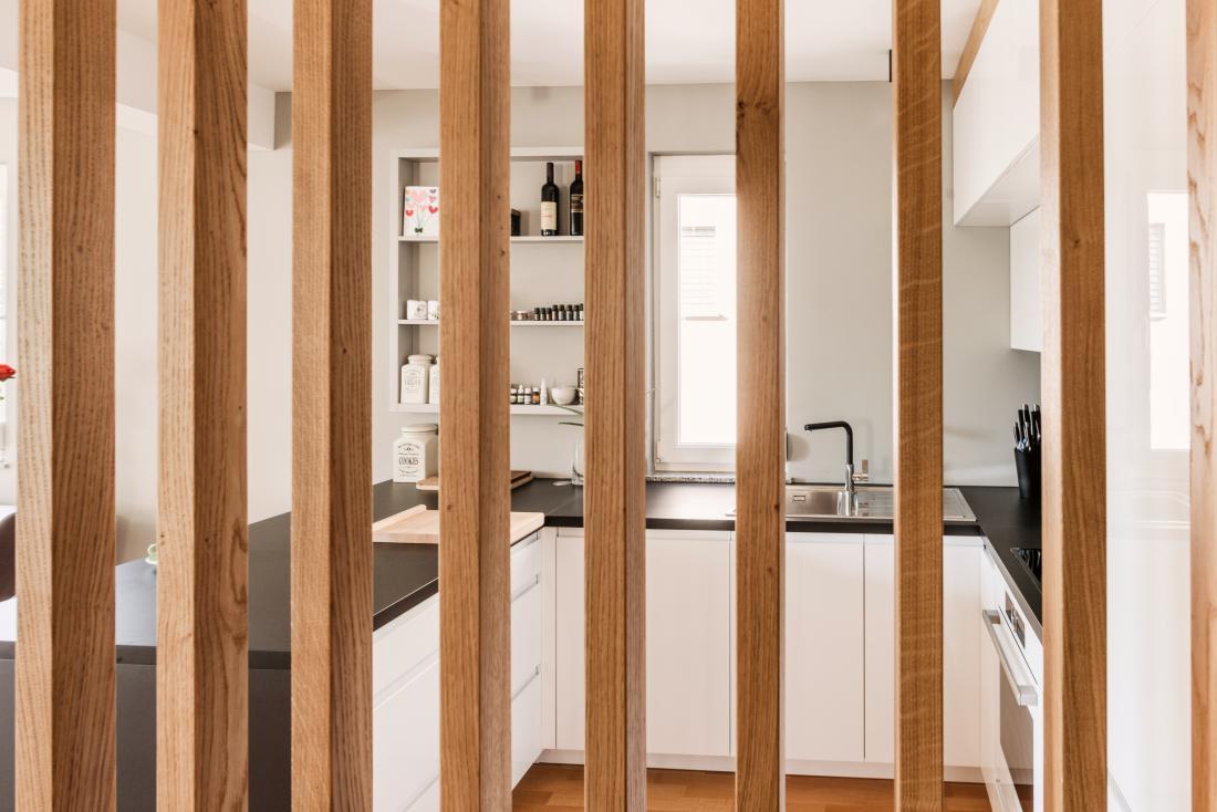 V spodnjem nadstropju mansarde so ob vhodu nameščene vertikalne lesene prečke, ki navidezno razmejijo vhod in kuhinjo.
