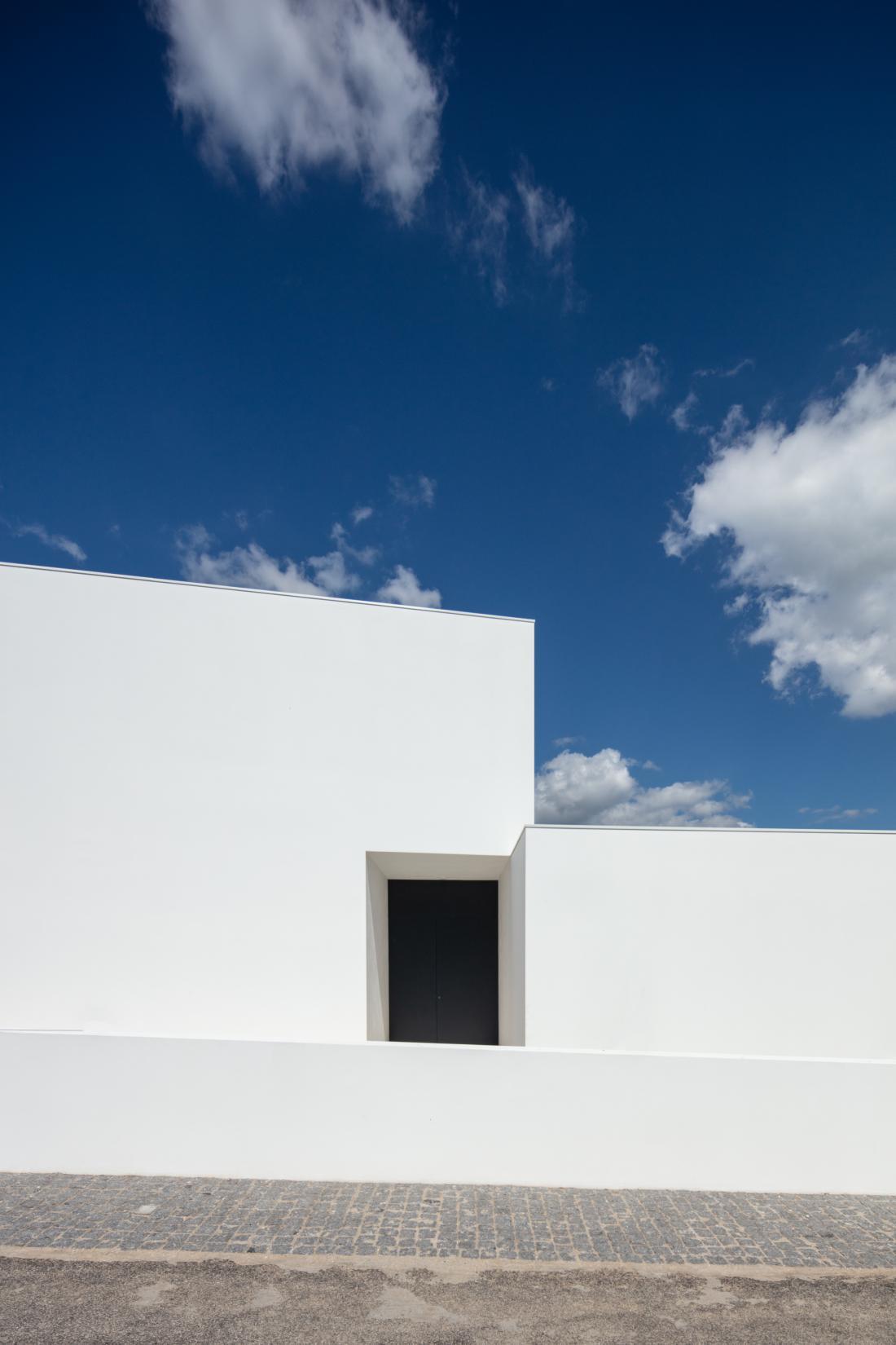 Ob cesti je hiša brez oken. Belo površino fasade prekinjajo le temna vhodna vrata.