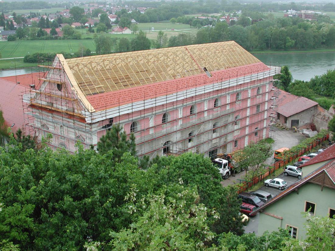 Opečna strešna kritina je še vedno najpogostejša izbira za pokrivanje dvokapne strehe. Na fotografiji prekrivanje cerkve dominikanskega samostana na Ptuju.