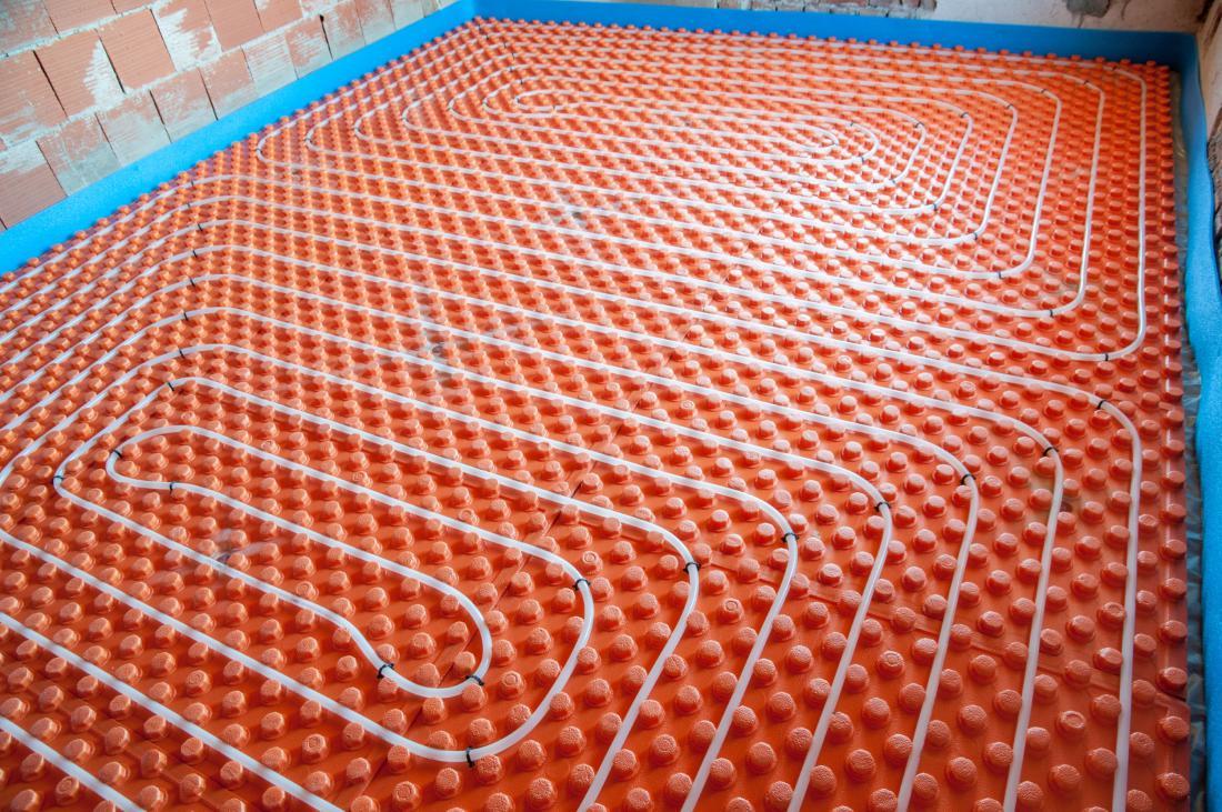 Sistemska plošča z vtisnjenimi čepki, ki pri enem od načinov polaganja olajšajo razporejanje cevi.