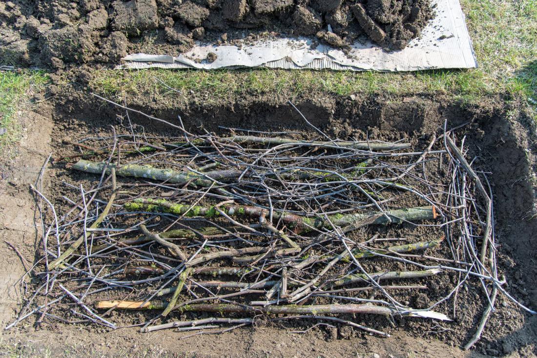 Nekateri odstranijo travno rušo in naložijo vejevje, preden začnejo postavljati konstrukcijo visoke grede. Foto: Eileen Kumpf/Shutterstock